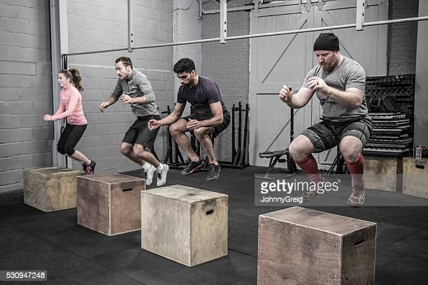 Four people doing box jumps in cross training class