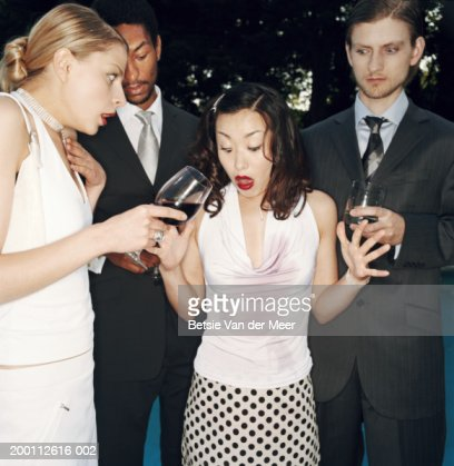 Four people holding drinks, young woman with red wine spilt down top