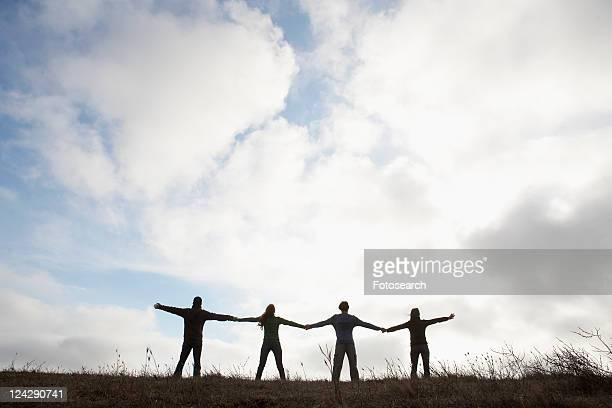 Four people holding hands in field (rear view, silhouette)