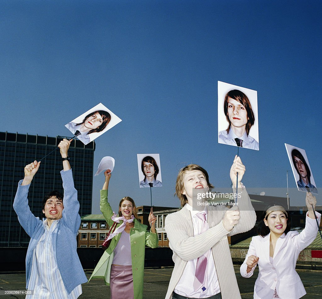 Four people holding up placards bearing identical image of man : Stock Photo