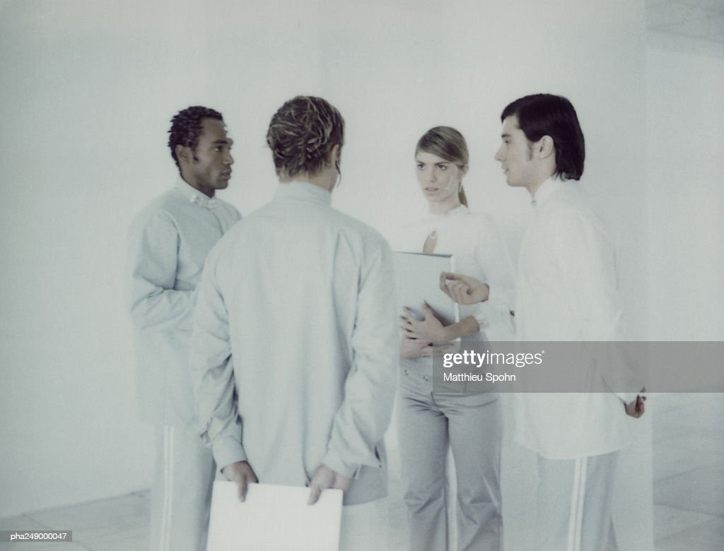 Four people in a room, talking : Stock Photo