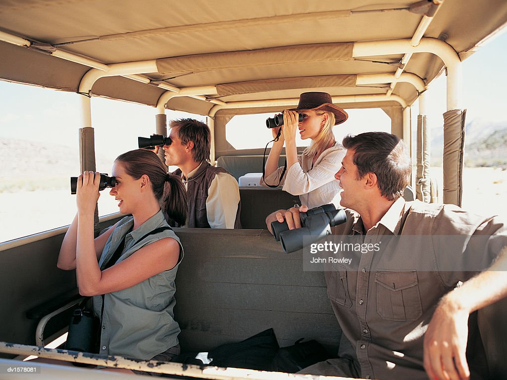 Four People In A Safari Bus Looking At The View Through