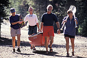 Four People Laughing and Carrying a Canoe and Paddles