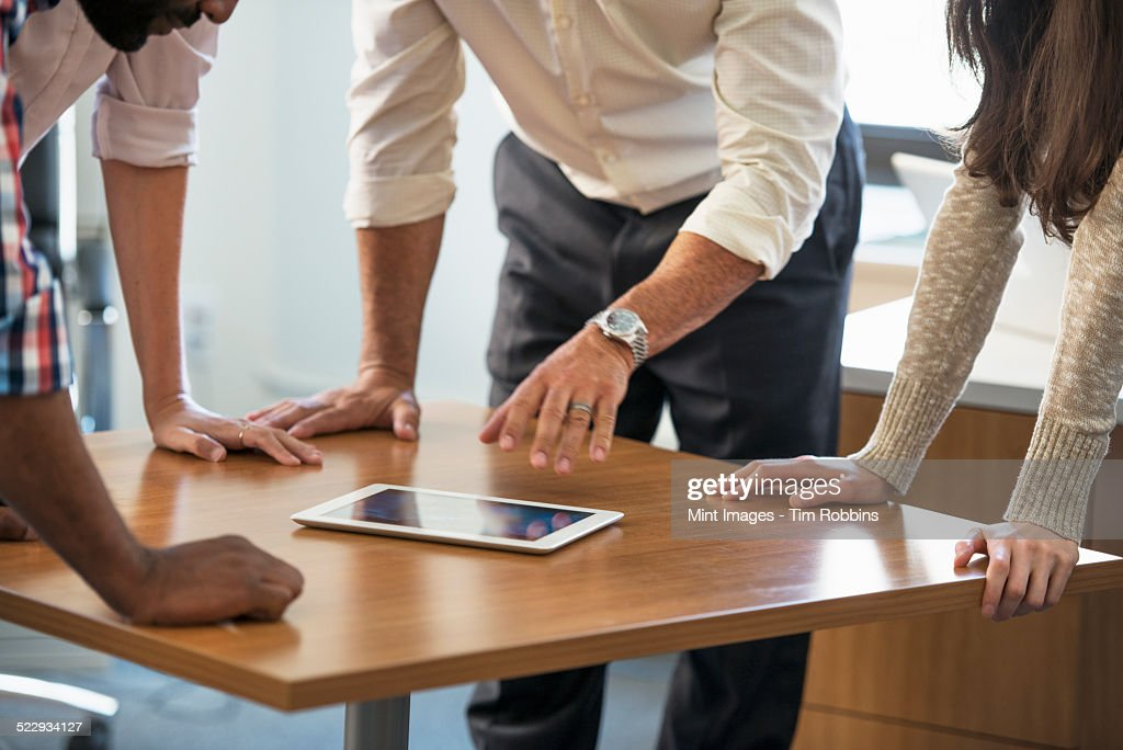 Four people leaning on a table at a meeting, looking at a digital tablet.