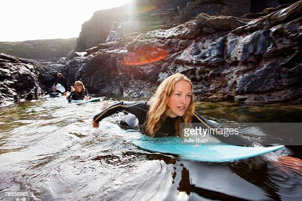 Four people lying on surfboards in the water smiling.