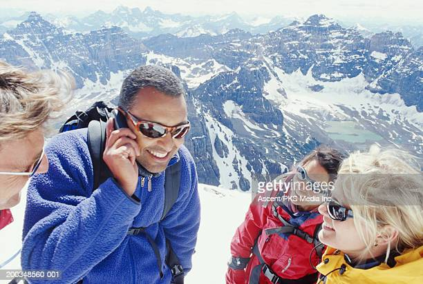 Four people on top of mountain, man speaking on mobile phone