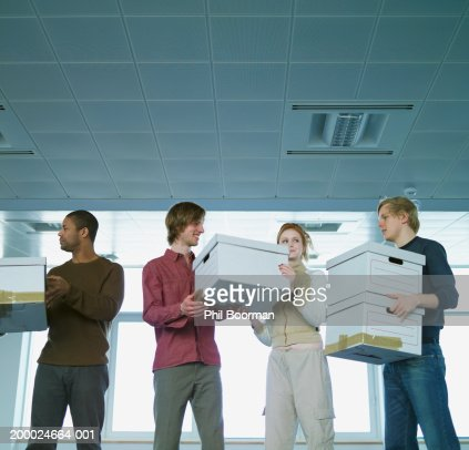 Four people passing packing boxes