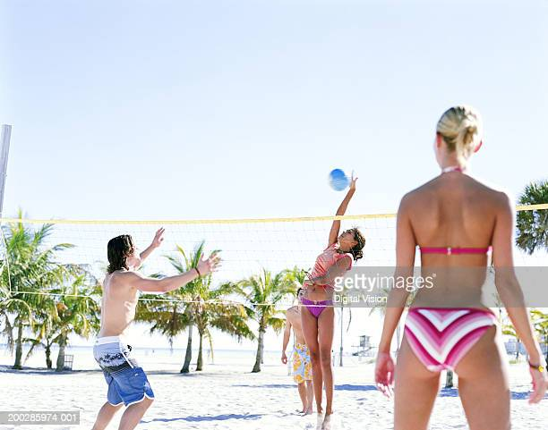 Four people playing volleyball on beach