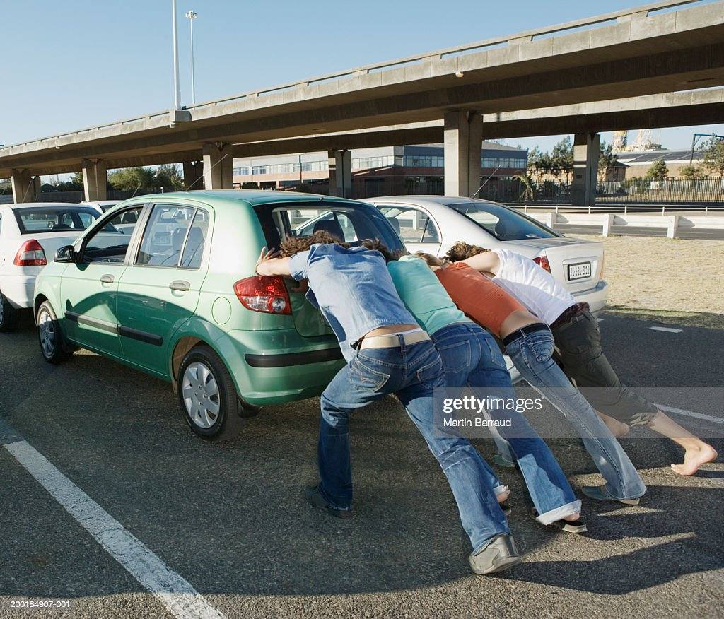 Four people pushing car on road, rear view : Stock Photo