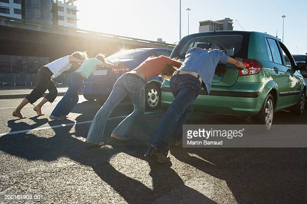 Four people pushing cars on road, rear view
