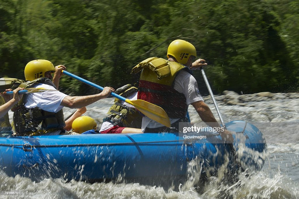 Four people rafting in a river : Foto de stock
