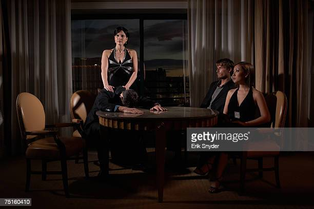 Four people sitting at round table in hotel room, one man with his face on table, woman standing behind him, evening