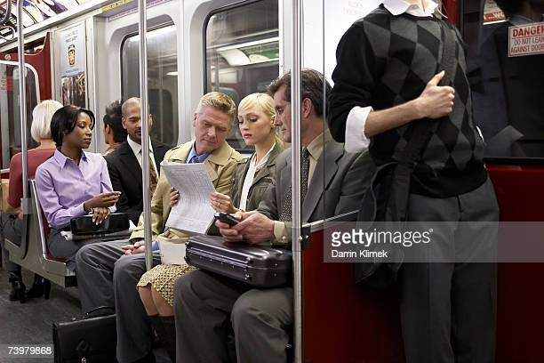 Four people sitting in subway train, woman reading newspaper