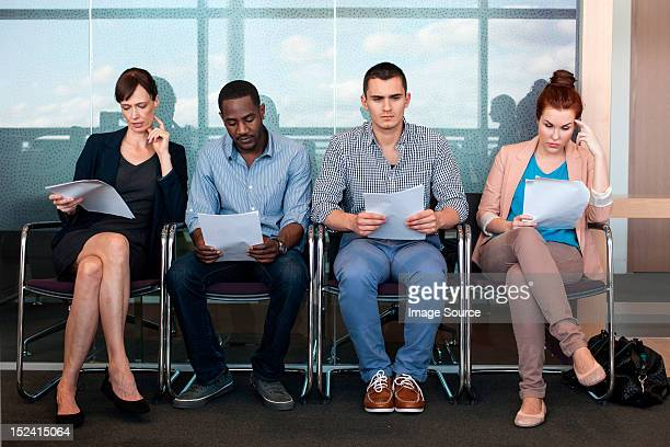 Four people sitting on chairs with documents