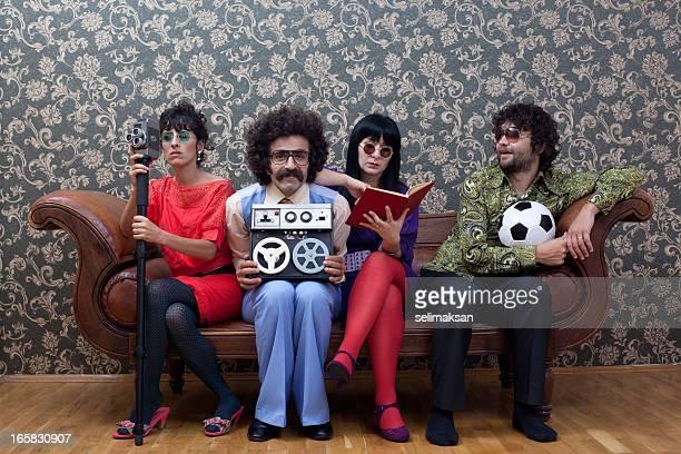Quattro persone seduto sul divano ciascuna dispone di vari hobby