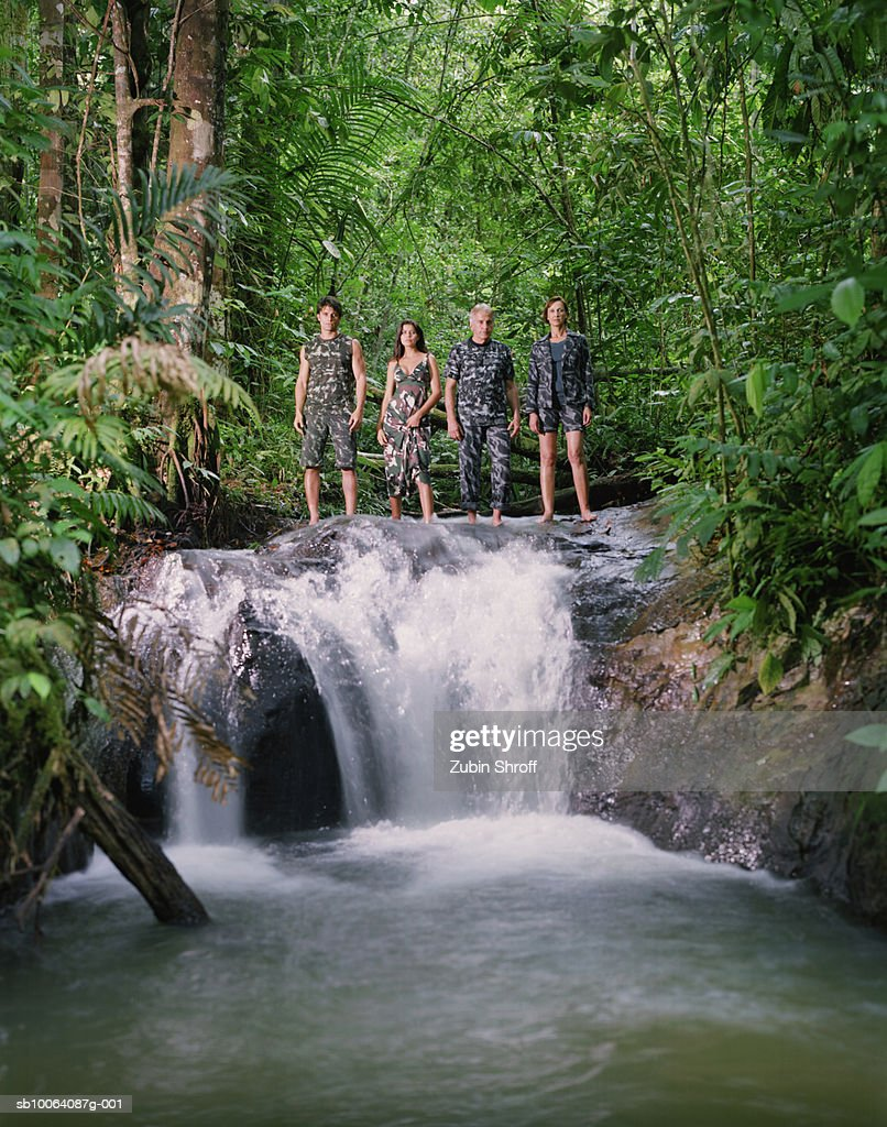 Four people standing at edge of waterfall in rainforest : Stock Photo
