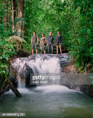Four people standing at edge of waterfall in rainforest : Foto de stock