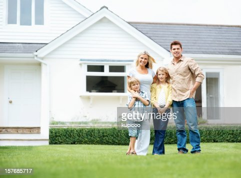 four people standing on lawn in front of their house