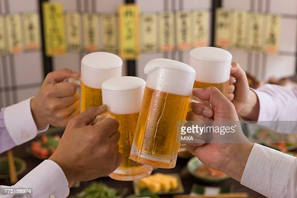 Four People Toasting with Beer at Izakaya