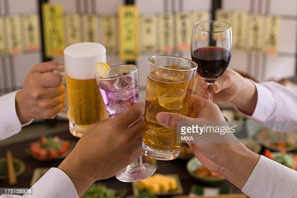 Four People Toasting with Each Other With Various Drinks at Izakaya