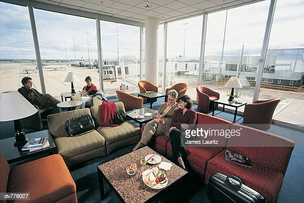 Four People Waiting in An Airport Lounge