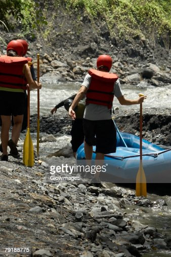 Four people walking towards an inflatable raft at a riverside : Stock Photo