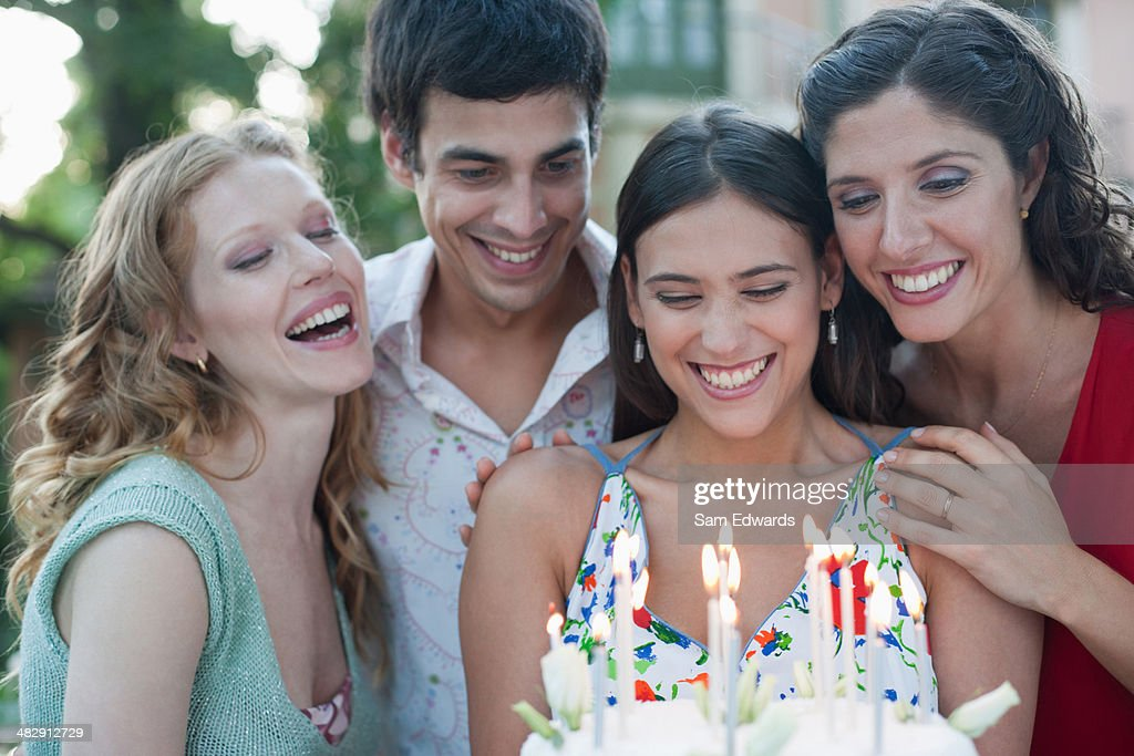 Four people with birthday cake at a party outdoors smiling