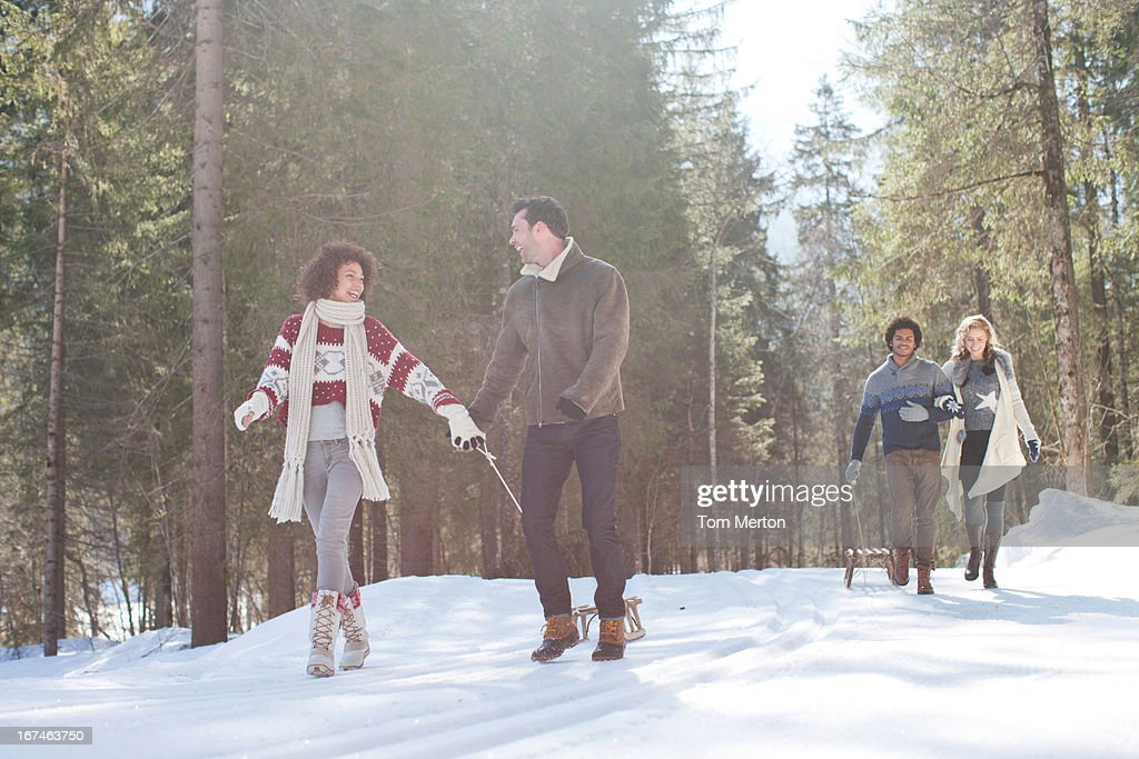 Four people with sled in snowy landscape : Stock Photo