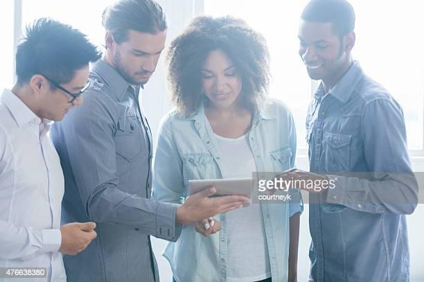 Vier Menschen arbeiten zusammen auf tablet PC in kleinen Business