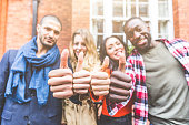 Four persons with different ethnicities showing thumbs up. Group of happy friends standing side by side, focus on the hands. Concepts of integration, multiculturalism and friendship.