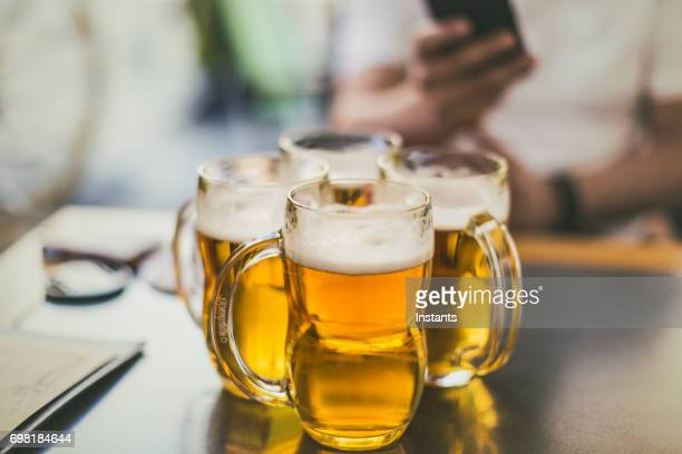 Four pilsner beer mugs on a table, as shot in Prague.
