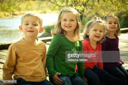 Four preschool age children sitting on bridge : Stock Photo