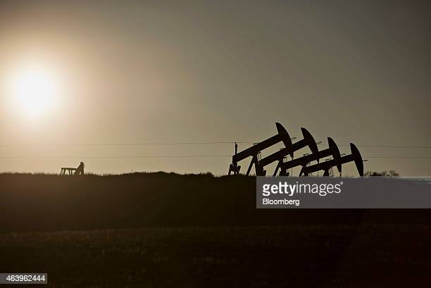 Four pumpjacks are silhouetted as they operate at the site of an oil well outside Williston North Dakota US on Thursday Feb 12 2015 A plunge in...