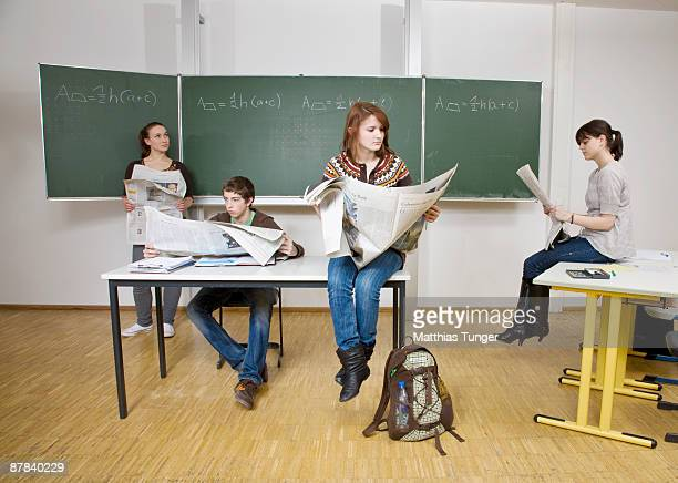 Four pupils sitting in classroom reading newspaper