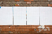 Four equal-sized billboards hang on a deteriorating wall.  The billboards do not have any images or text on them, and they are covered with white paper.  The section of the block wall above the billbo