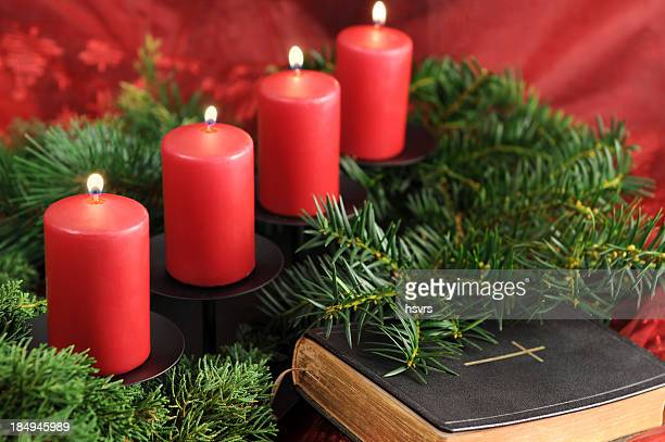 four red Advent candle burning with bible in front