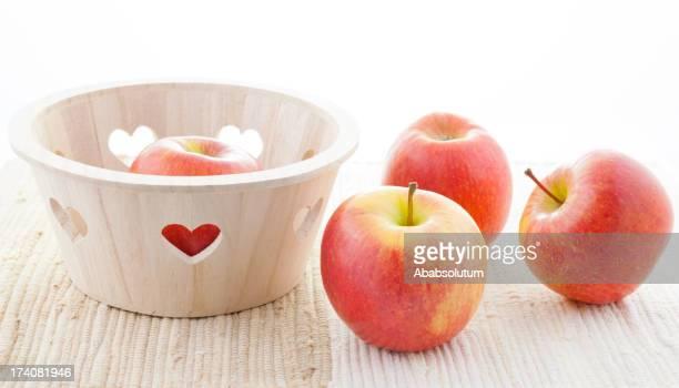 Vier Rote Kiku Äpfel und Korb mit Herz