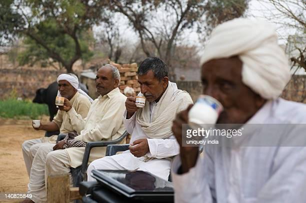 Four rural men drinking tea in a village, Hasanpur, Haryana, India