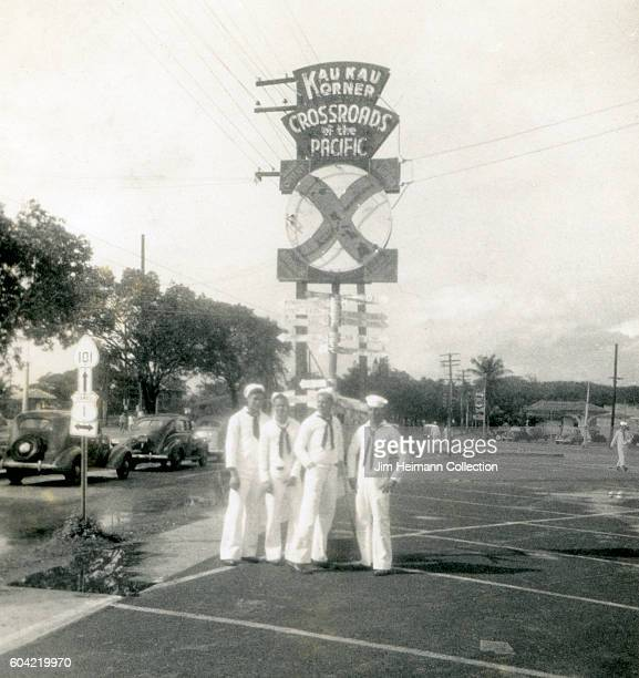 Four sailors standing at Kau Kau Korner Crossroads of the Pacific sign