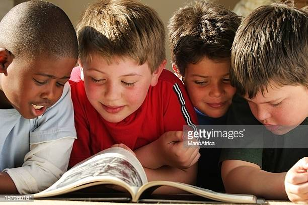 four schoolboys reading