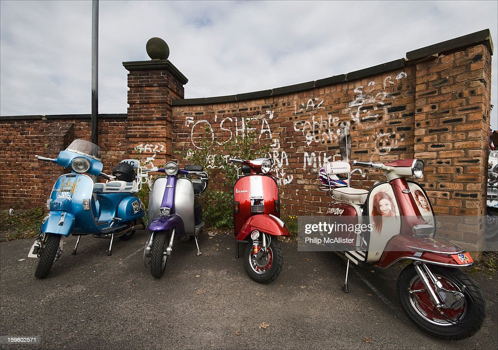 CONTENT] Four scooters,two Lambrettas and two Vespas are parked against a brick wall.The wall has graffiti on it.