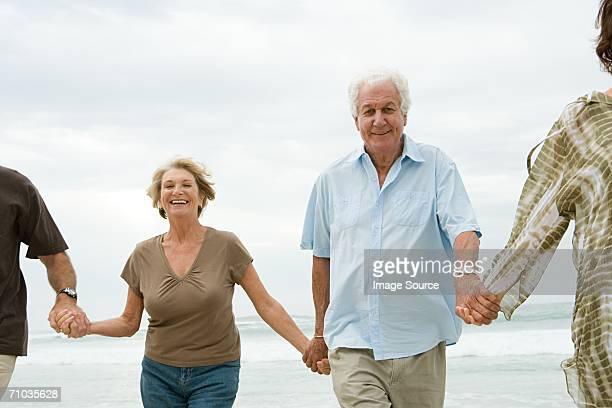 Cuatro adultos senior sosteniendo las manos en la playa