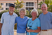 Four senior friends standing together and smiling