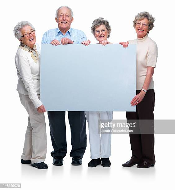 Four senior man and women holding placard