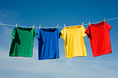 a red, green, blue and yellow t-shirt hanging on a clothesline in front of a blue sky, add text or graphic to the shirts