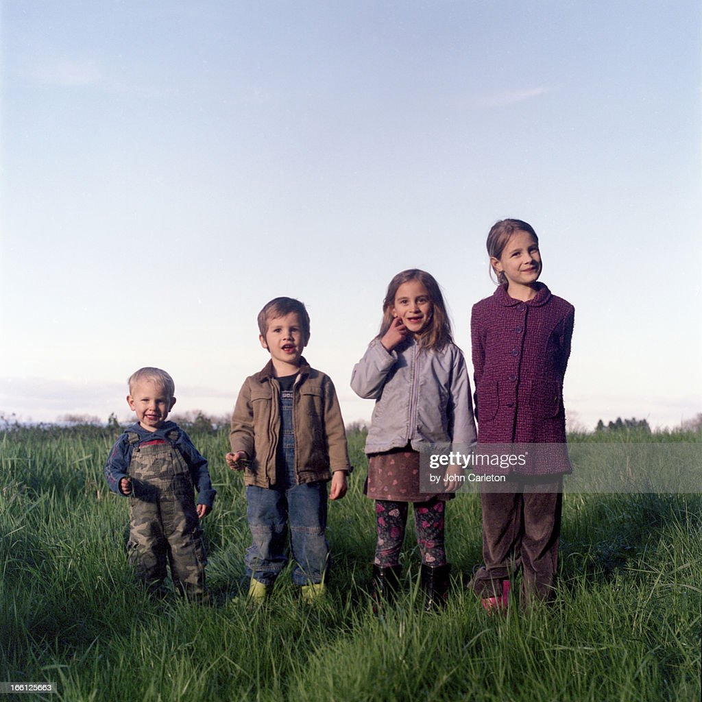 Four siblings in ascending height : Stock Photo