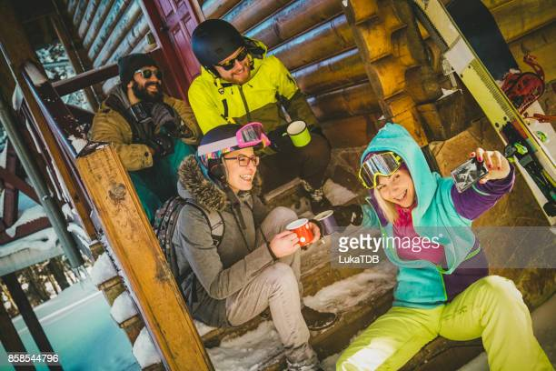Four ski people taking a selfie in front of cottage
