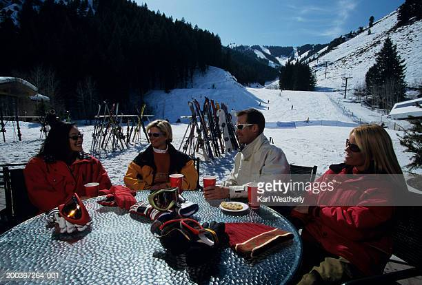 Four skiers sitting at table