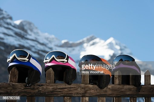Four skiing helmets on wooden fence