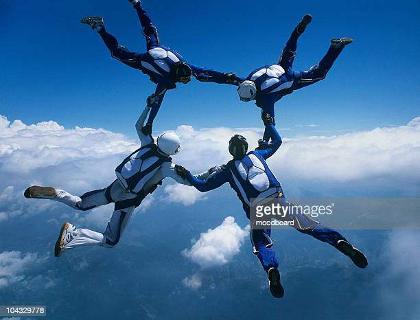 Four skydivers holding hands in ring against clouds